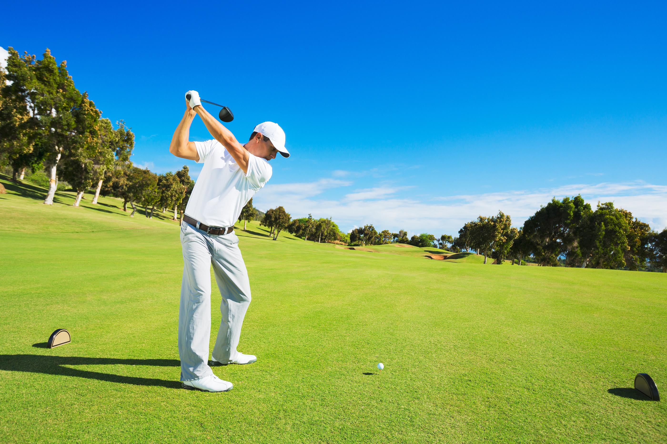Golf player teeing off. Man hitting golf ball from tee box ...